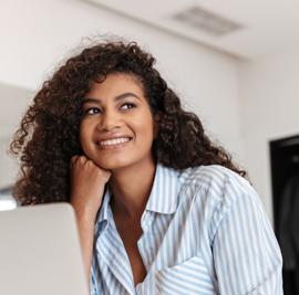femme pensive sourit ordiinateur