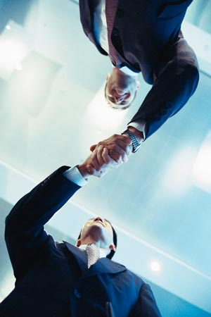 hommes costume se serrent la main